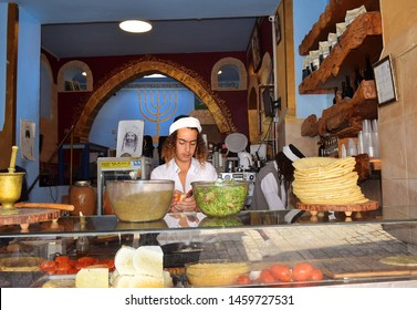 Safed, Upper Galilee, Israel - July 19, 2019: young sephardic religious jew, working as a cook in a kosher cafe in the quarter of artists in the old town of Safed