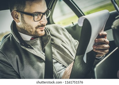 It is safer to read the contract first. Business man sitting in car and reading document. Close up.