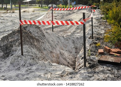 Safety barrier in place to stop people falling into a hole.Safety flagging on four star pickets, enclosing an excavation in sand, for site works for a residential building.
