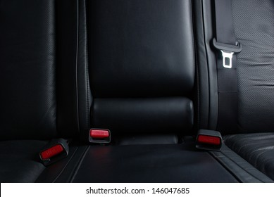 Safety buckle on the black leather seat in a car