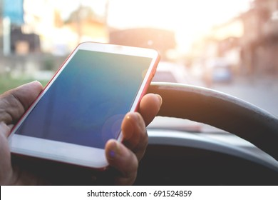 Safety concept, The driver holds and uses mobile phone while driving and have truck in front of the car.
