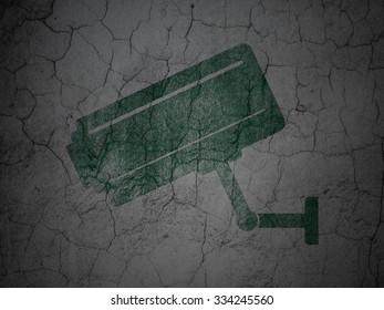 Safety concept: Green Cctv Camera on grunge textured concrete wall background