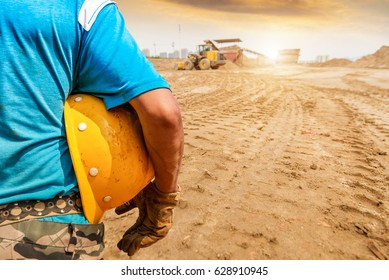 Safety Construction Concept , Safety engineer holding yellow hardhat and Loader  backhoe  truck background.