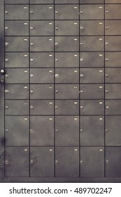Safety deposit box wallpaper. Numerous secure safety deposit boxes with lock and number plate. Black metal. Insurance banking concept.  Abstract business concept.