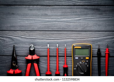 Safety electric tools on black wooden background. Tester, screwdrivers and nippers with space for text on wood backdrop.