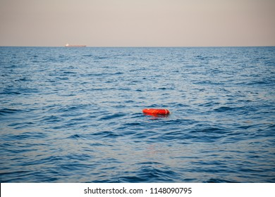 Safety equipment, life buoy or rescue buoy ring with a rope floating in blue sea to rescue people. Yachting, marine background