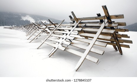 Safety fence against snow storm. Snow-fence in winter landscape, by the road.