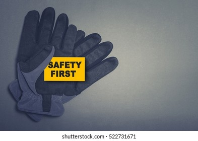 Safety first card in protective gloves on dark background