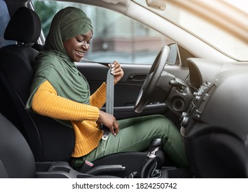 Safety First. Smiling Black Muslim Woman In Hijab Fastening Seatbelt In Her Car Before Driving In City, Following Safe Ride Rules, Ready For Travel With Auto, Side View With Free Space