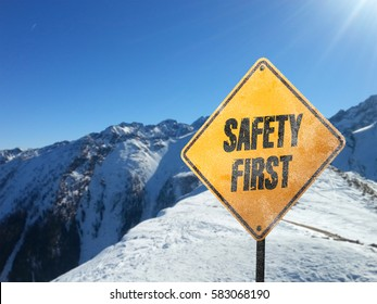 Safety First, yellow frosted warning sign with snow, sun, blue sky and mountains in the background