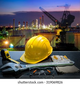 Safety gear kit and tools standing in front of oil refinery background