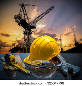 Safety gear kit and tools standing in front of construction site background concept