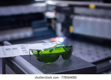 Safety glasses lie on the background of a laser cutting metal sheet