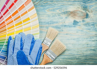 Safety gloves color sampler paint brushes on wooden board construction concept.