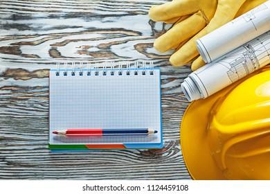 Safety gloves hard hat blueprints notepad pencil.