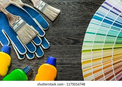 Safety gloves paint brushes bottles pantone fan on wooden board.