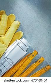 Safety gloves rolled blueprints wooden meter on concrete backgro