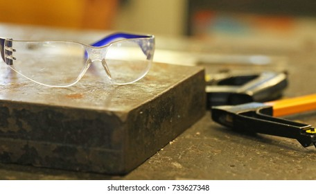 Safety goggles in the industrial technology workshop  with tools. Factory trade concept personal health safety in the workshop. Down tools. metal sheet worker.