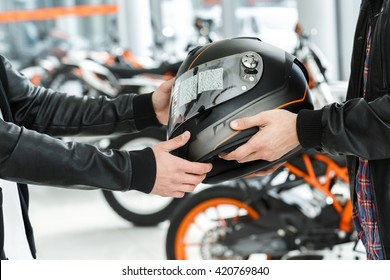 Safety guarantee. Cropped shot of a motorcycle salon manager passing a helmet to his customer at the motorbike salon