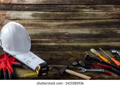 Safety hard hat, architect blue print and professional hardware tools on rustic wooden blank background for DIY and maintenance banner