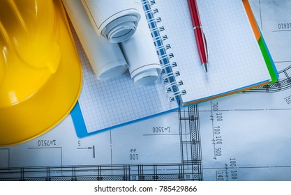 Safety hard hat checked notebook pen blueprints on construction plan.