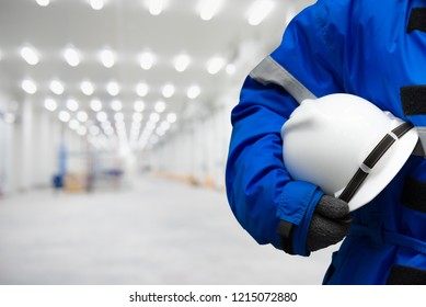 Safety hardhat for dangerous accident protection in warehouse during work. Cold room storage and freezing warehouse. copy space for text.