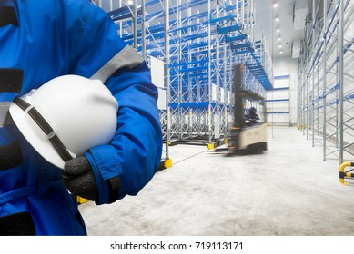 Safety hardhat for dangerous accident protection in warehouse during work. Cold room storage and freezing warehouse with stacker truck inside moving.