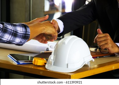Safety hat on wooden table with business man is shaking hand with engineer behind