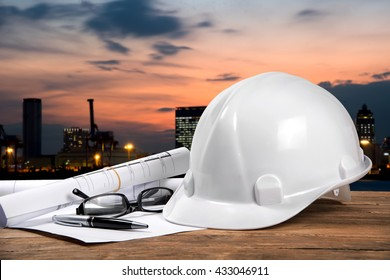 safety helmet and architect plant on wood table with city sunset scene and building construction