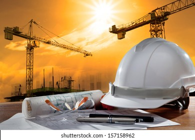 safety helmet and architect working  table against  building construction