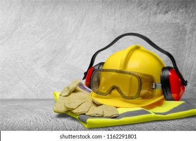 Safety helmet with earphones and goggles on construction background