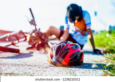safety helmet lost off from woman bicyclist and splatter away from head after accident clashed impact on the street road, injuried hurt on accident