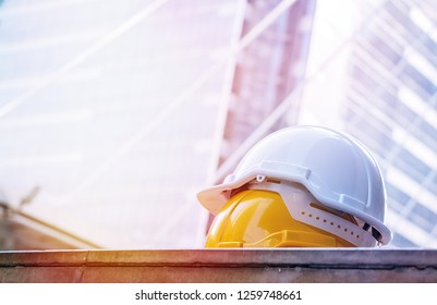 Safety helmet on the floor with building background.A hard hat is a type of helmet predominantly used in workplace environments such as industrial or construction sites to protect the head from injury