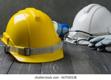 Safety helmet with other standard safety tools on dark wood background.