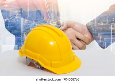 Safety helmet stacked in  background Double exposure of handshake and city background Security Collaborative Concepts
