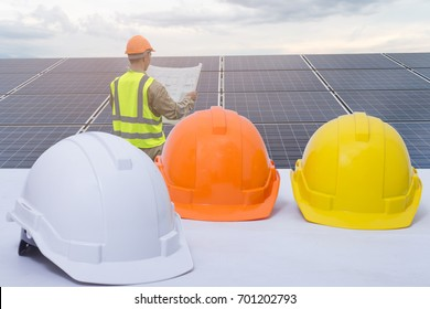 Safety helmet stacked  district. Engineers checking solar panels, on the Solar Panel. in the background