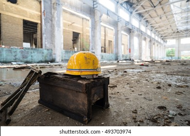 Safety helmet standing in front of Abandoned metallurgical factory interior and building waiting for a demolition.