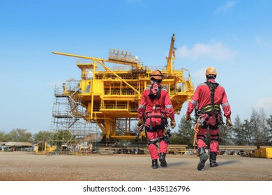 Safety man walking wearing equipment full safety harness,safety line working, Worker Demonstration the sprinkling of high wear equipment protective PPE on Construction site rig Oil refinery.