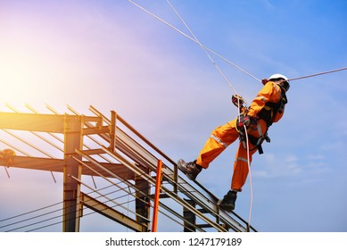 Safety man worker sprinkle with equipment safety harness on steel construction site and building structure frame with blue sky background