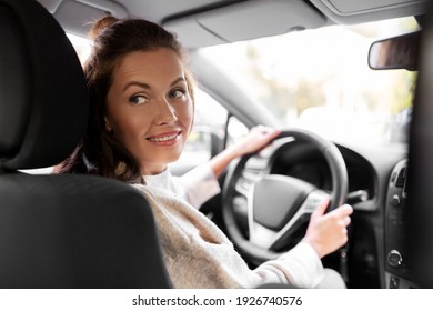 safety and people concept - happy smiling young woman or female driver driving car in city