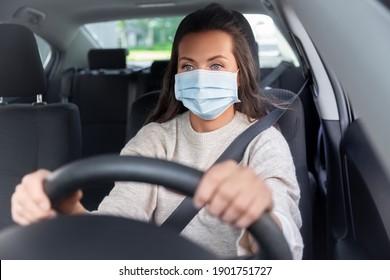 concepto de seguridad y personas - joven conductor o mujer con mascarilla médica conduciendo un coche en la ciudad