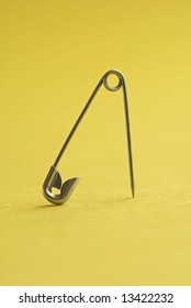 Safety Pin against a yellow background