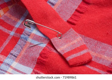 Safety pin fastening pieces of a bright, red, blue colored cotton fabric together