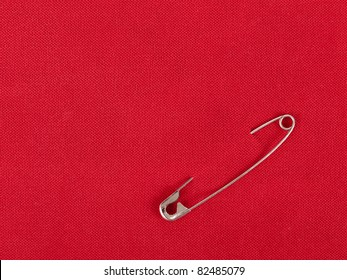 Safety pin in red fabric swatch for background