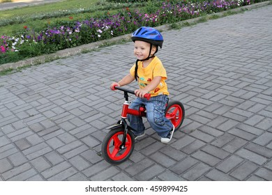 Safety and protection when doing cycling stunts. Early harmonious physical development of children. Little emotional boy in white helmet and jeans riding down the road on your children's red bike