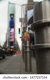 Safety pylons along sidewalk in Times Square, NY to protect people walking through tourist attraction from traffic accidents and reduce terror threats to location area with trucks and vehicles
