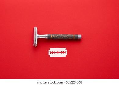safety razor and shaving brush on red background