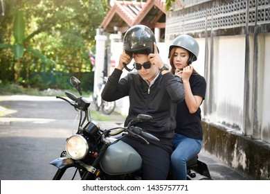 Safety riding concept. Asian Couple, Male and female biker or motorcyclist wearing safe helmet before travel on motorcycle as accident prevention.