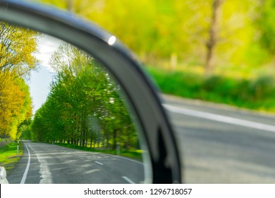 Safety road check in rear vision mirror while driving scenic South Island road, New Zealand