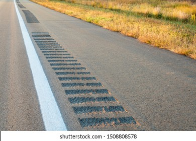 safety rumble strips on a highway shoulder to reduce run-off-road collisions, driving safety concept